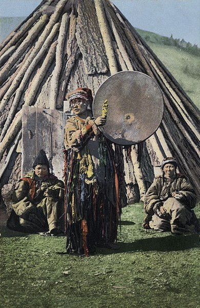 Altai shaman with a tambourine on the background of a traditional dwelling - chaadyr